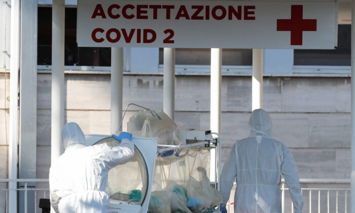 Medical workers in protective suits push an isolation stretcher in front of the Columbus Clinic, where patients suffering from COVID-19 were moved from Spallanzani Hospital in Rome, Italy, on March 16, 2020. (Remo Casilli/Reuters)