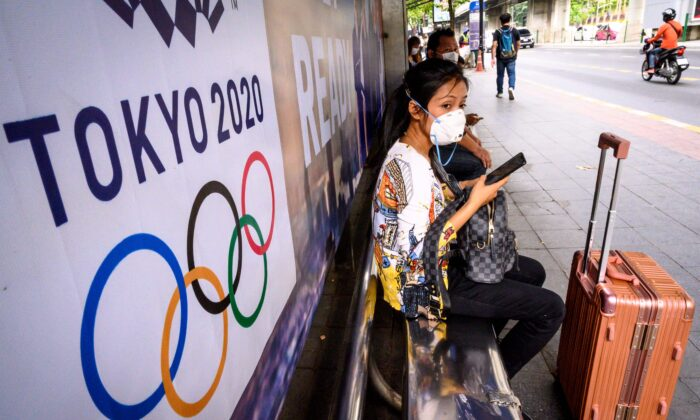 A woman with a suitcase wearing a facemask, amid concerns over the spread of COVID-19, sits at a bus stop in front of a Tokyo 2020 Olympics  advertisement in Bangkok, Thailand, on March 16, 2020. (Mladen  Antonov/AFP via Getty Images)