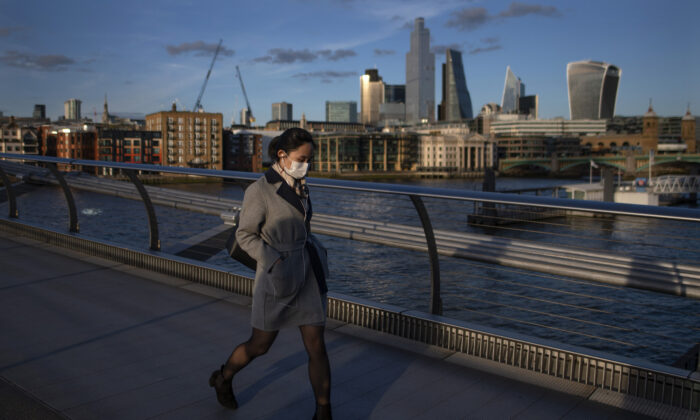 A woman crosses the millennium bridge wearing a face mask for protection against the corona virus in London, England on March 16, 2020. (Justin Setterfield/Getty Images)