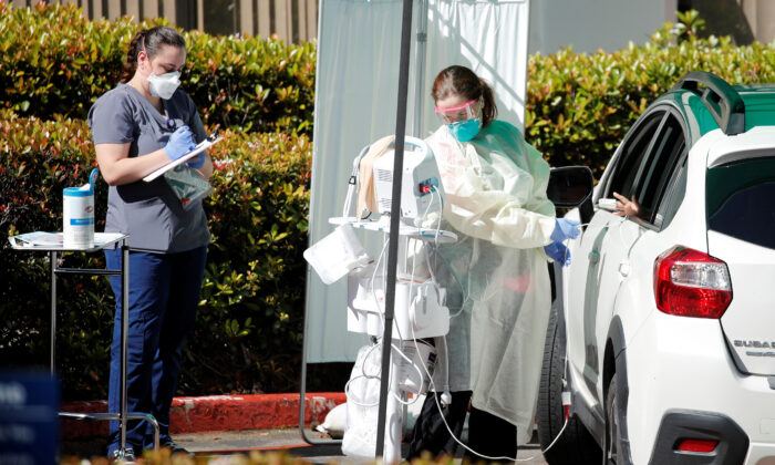 A health care worker attends to a person at a drive-up care facility in response to the outbreak of COVID-19, in La Jolla, Calif., on March 17, 2020. (Mike Blake/Reuters)