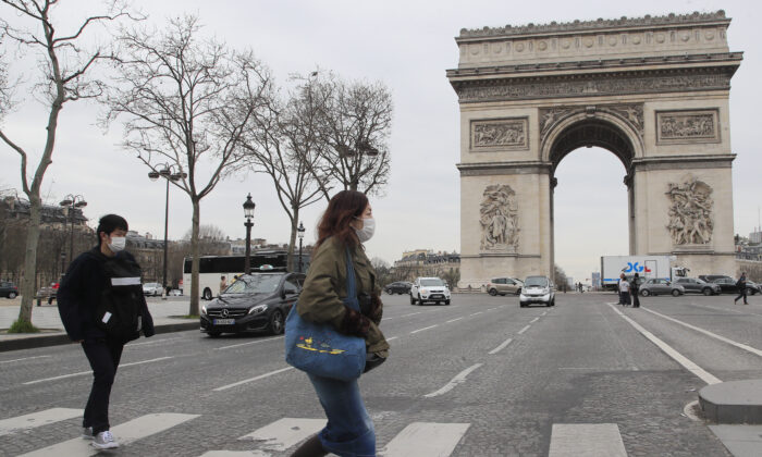 Tourist cross the Champs Elysees avenue in Paris, Monday, March 16, 2020. (AP Photo/Michel Euler)