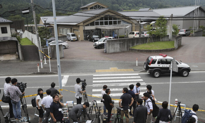 Journalists gather in front of Tsukui Yamayuri-en, a facility for the handicapped where a former care home employee killed disabled people, in Sagamihara, outside Tokyo. (Eugene Hoshiko/AP)