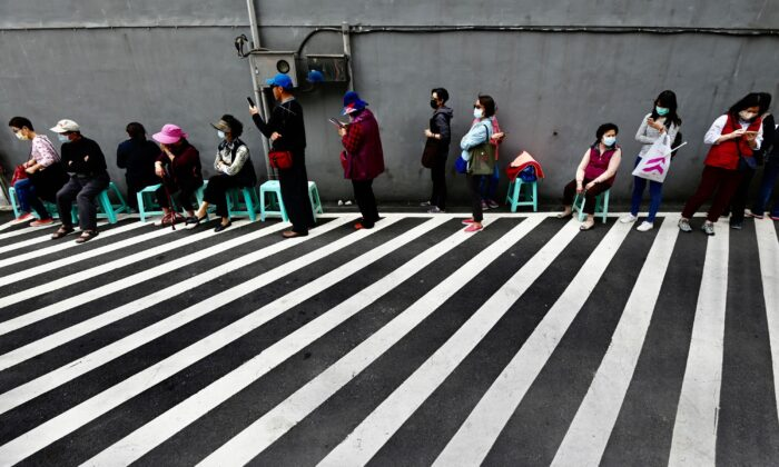 Local residents line up to buy face masks, amid concerns of the COVID-19 coronavirus, from a pharmacy in New Taipei City, Taiwan, on March 17, 2020. (Sam Yeh/AFP via Getty Images)