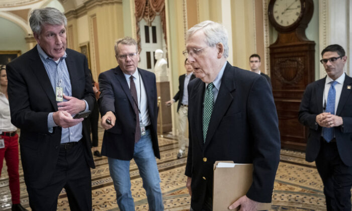 Reporters ask questions as Senate Majority Leader Mitch McConnell (R-Ky.) walks to the Senate floor at the U.S. Capitol in Washington on March 16, 2020. (Drew Angerer/Getty Images)
