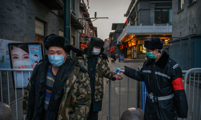 A Chinese man wears a protective mask as he and others have their temperature checked by a guard at a temporary entrance to a commercial area in Beijing on March 11, 2020. (Kevin Frayer/Getty Images)