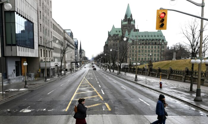 People cross a largely deserted Wellington Street, the major street in front of Parliament Hill in Ottawa, on March 17, 2020. T(he Canadian Press/Justin Tang)