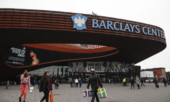 Pedestrians walk past the Barclays Center, which is home to the Brooklyn Nets, in the Brooklyn borough of New York City on March 12, 2020. (John Minchillo/AP Photo)