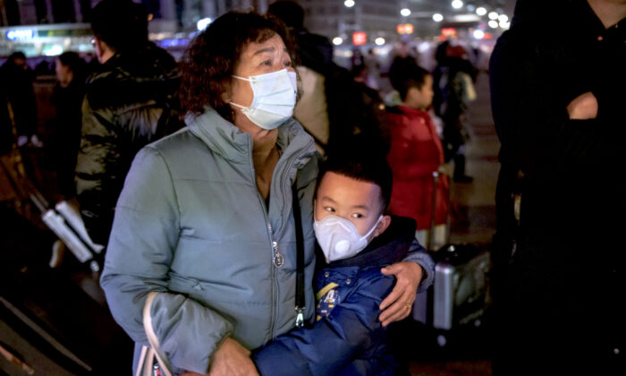 A Chinese boy hugs a relative as she leaves to board a train at Beijing Railway station in Beijing, China, on Jan. 21, 2020. (Kevin Frayer/Getty Images)