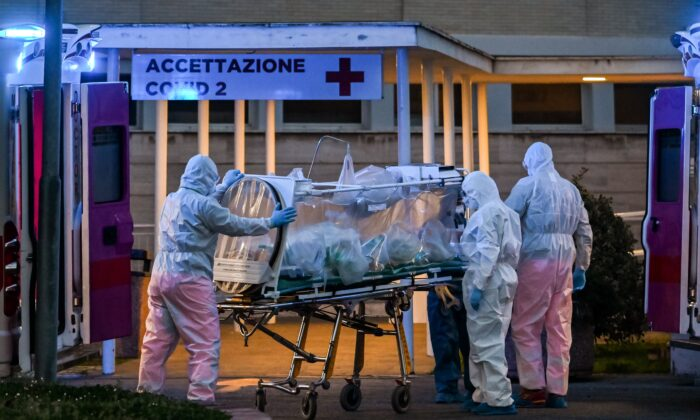 Medical workers in overalls stretch a patient under intensive care into the newly built Columbus Covid 2 temporary hospital to fight the new coronavirus infection, at the Gemelli hospital in Rome on March 16, 2020. (Andreas Solaro/AFP via Getty Images)