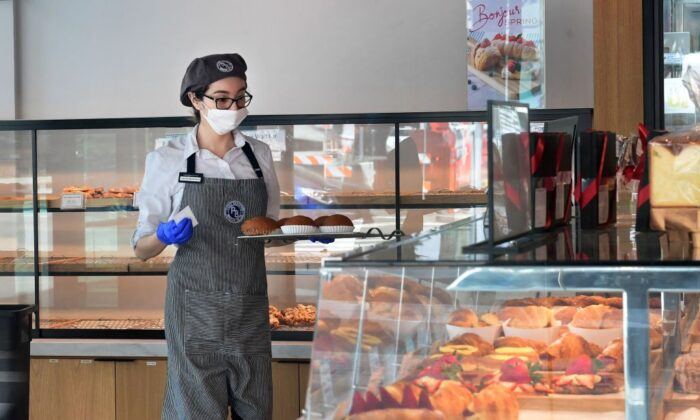 An employee at a cafe and bakery wears a facemask in Los Angeles, Calif., on March 17, 2020. (Frederic J. Brown/AFP via Getty Images)