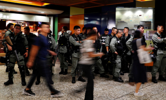 Riot police wait at a Mass Transit Railway (MTR) station as commuters walk past to catch a subway train, in Hong Kong, China, on Sept. 2, 2019. (Anushree Fadnavis/Reuters)