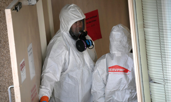 A cleaning crew wearing protective clothing enters a long-term care facility where a COVID-19 outbreak occurred, on March 12, 2020 in Kirkland, Washington. (John Moore/Getty Images)