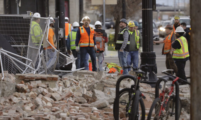 Construction workers looks at the rubble from a building after an earthquake in Salt Lake City, Utah, on March 18, 2020. (AP Photo/Rick Bowmer)