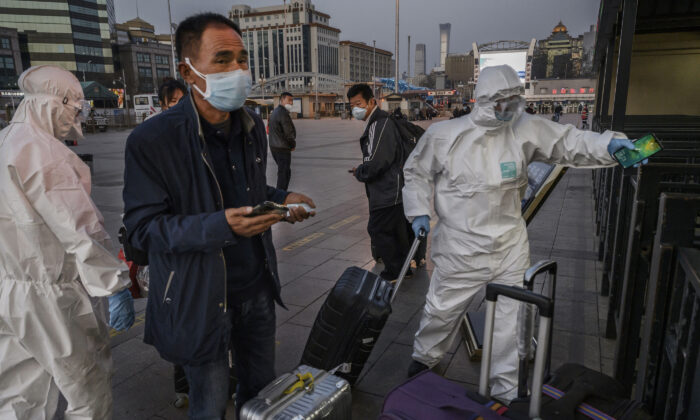 People wear protective masks and clothing as they arrive at Beijing Railway Station in Beijing, China, on March 13, 2020. (Kevin Frayer/Getty Images)