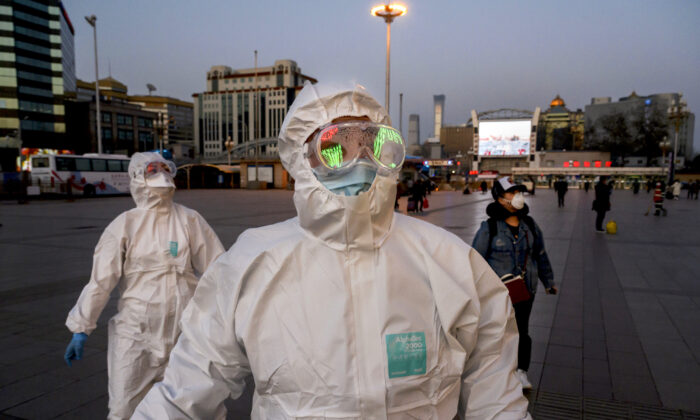 Two persons wearing protective masks and suits arrive at Beijing Railway Station on March 13, 2020.   (Kevin Frayer/Getty Images)