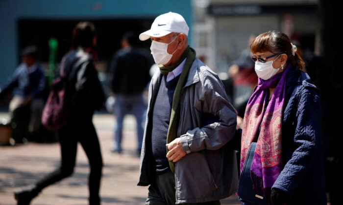 People walk on the street, wearing protective masks as a preventive measure against the spread of the coronavirus disease (COVID-19), in Bogota, Colombia March 17, 2020. (Reuters/Leonardo Munoz)