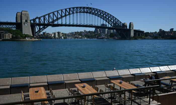 Tables at an open restaurant are seen mostly deserted on a quiet morning at the waterfront of the Sydney Opera House, where scheduled public performances have been cancelled due to the coronavirus disease (COVID-19), in Sydney, Australia, March 18, 2020. (Reuters/Loren Elliott)