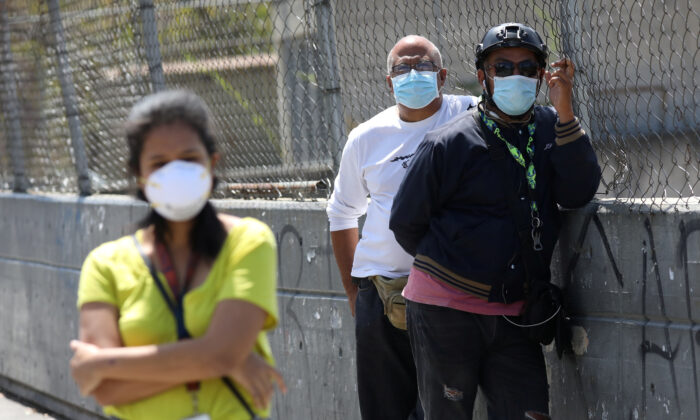 People wearing protective masks on the streets after the start of quarantine in response to the spread of coronavirus disease (COVID-19) in Caracas, Venezuela March 17, 2020. {Manaure Quintero/Reuters)