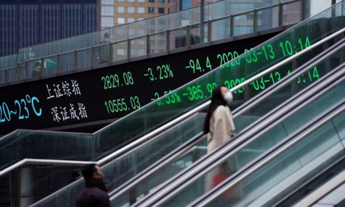 Pedestrians wearing face masks ride an escalator near an overpass with an electronic board showing the Shanghai and Shenzhen stock indexes, following an outbreak of the novel coronavirus in the country, at Lujiazui financial district, in Shanghai, China, on March 13, 2020. (Aly Song/Reuters)