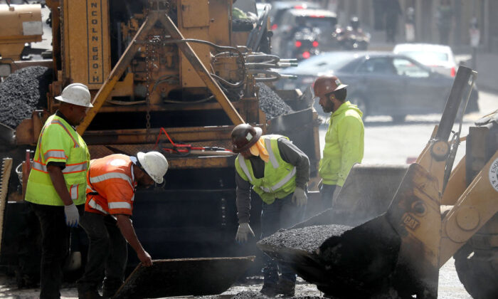 Construction workers smooth tar as they pave a road in San Francisco on Oct. 5, 2018. (Justin Sullivan/Getty Images)