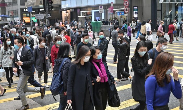 Pedestrians wearing face masks in Hong Kong on March 12, 2020. (Antony Wallace/AFP via Getty Images)