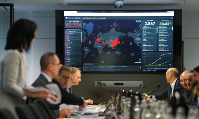 Members of Germany's coronavirus emergency task force sit down for a work session while a monitor shows the global spread and human toll of the virus at offices of the Ministry of Health on Feb. 28, 2020 in Berlin, Germany. (Sean Gallup/Getty Images)