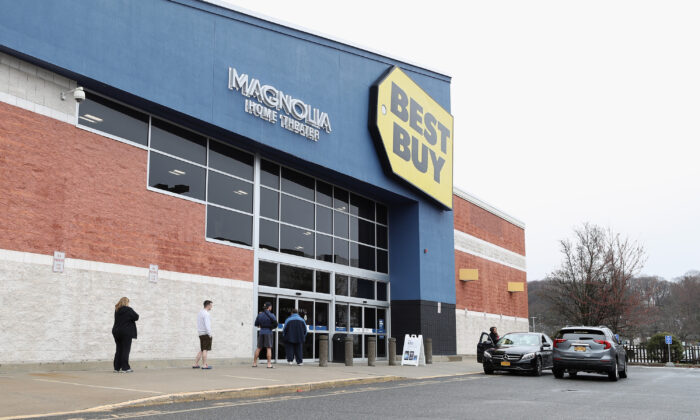 People wait in line at a Best Buy while observing social distancing as customers are allowed to enter a couple at a time while the coronavirus continues to spread across the United States in Huntington Station, N.Y., on March 19, 2020. (Bruce Bennett/Getty Images)