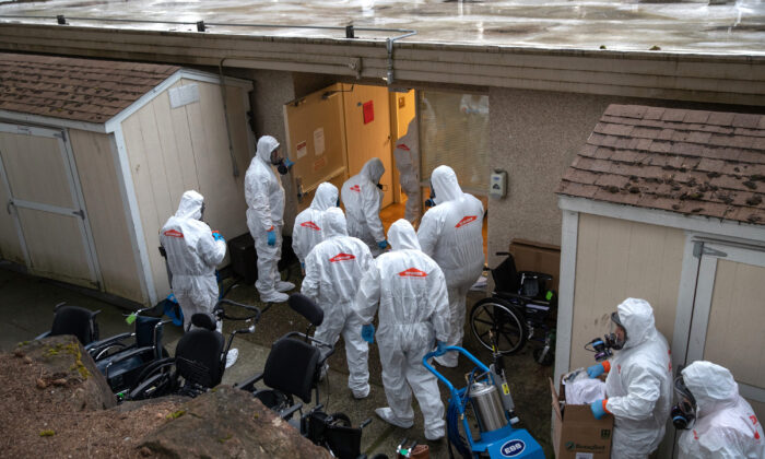 A cleaning crew wearing protective clothing enters a long-term care facility where a COVID-19 outbreak occurred n Kirkland, Washington, on March 12, 2020. (John Moore/Getty Images)