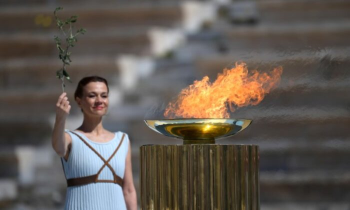 An athlete lights the Olympic torch during the olympic flame handover ceremony for the 2020 Tokyo Summer Olympics, in Panathenaic Stadium, Athens, Greece, on March 19, 2020. (Aris Messinis/Pool via Reuters)