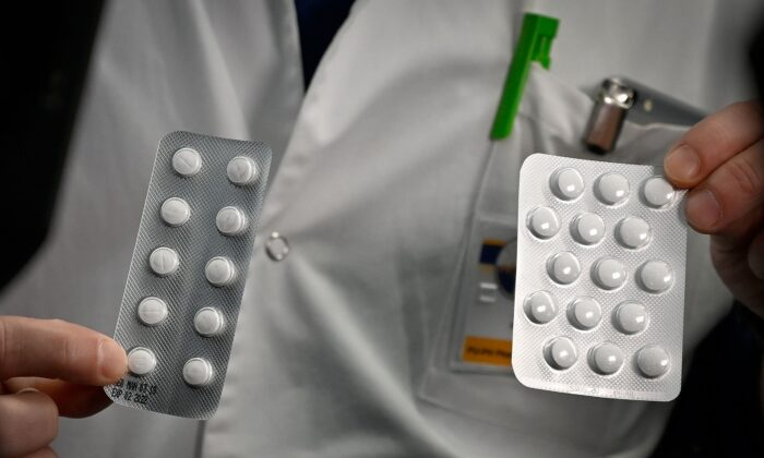 A staff member shows packets of Nivaquine tablets containing chloroquine and Plaqueril tablets containing hydroxychloroquine at the IHU Mediterranee Infection Institute in Marseille, France, on Feb. 26, 2020. (Gerard Julien/AFP via Getty Images)