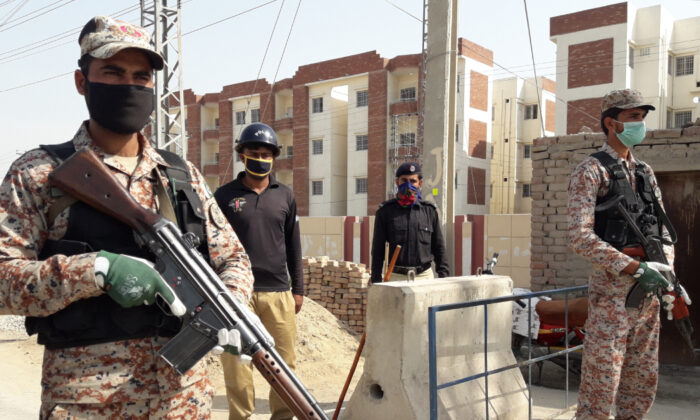 Pakistani security personnel stand guard outside apartments that were converted to a quarantine facility for people suspected of being exposed to the coronavirus after having travelled to Iran, in Sukkar, Pakistan, Tuesday, March 17, 2020. (Pervez Khan/AP)