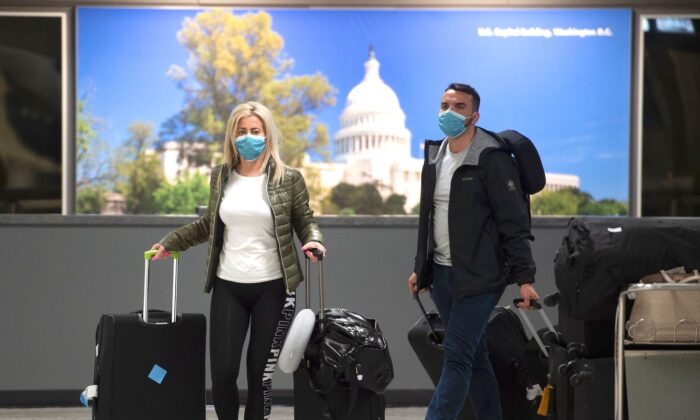 Passengers wear masks as they arrive at Dulles International airport in Dulles, Virginia, on March 17, 2020. (Andrew Caballero-Reynolds/AFP via Getty Images)
