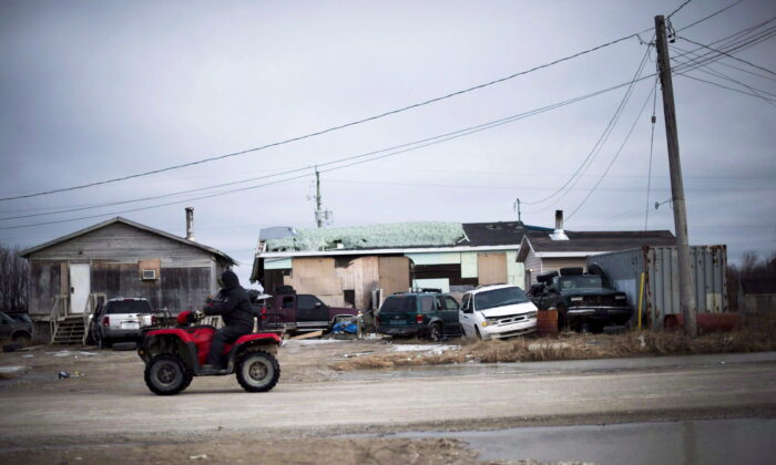 A man rides his ATV in the northern Ontario First Nations reserve in Attawapiskat, Ont., in a file photo. (The Canadian Press/Nathan Denette)