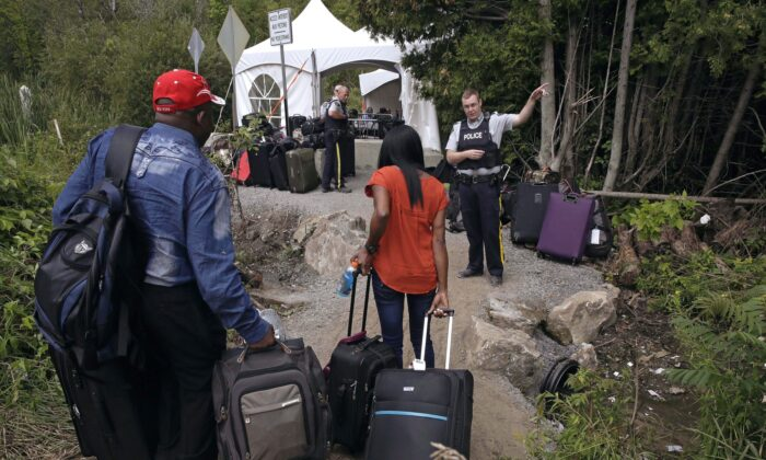 An RCMP officer informs a migrant couple of the location of a legal border station, shortly before they illegally crossed from Champlain, N.Y., to Saint-Bernard-de-Lacolle, Quebec, via Roxham Road. (AP Photo/Charles Krupa, File)