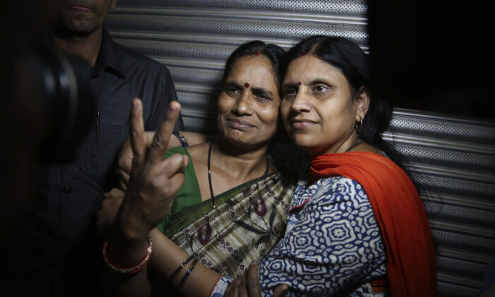Asha Devi (L) mother of the victim of the fatal 2012 gang rape on a moving bus, displays a victory sign with her sister after the rapists of her daughter were hanged, in New Delhi, India, on March 20, 2020. (Altaf Qadri/AP Photo)