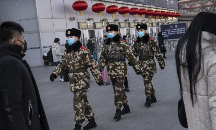 Chinese police officers wear protective masks as they patrol before the annual Spring Festival at a Beijing railway station on Jan. 23, 2020. (Kevin Frayer/Getty Images)
