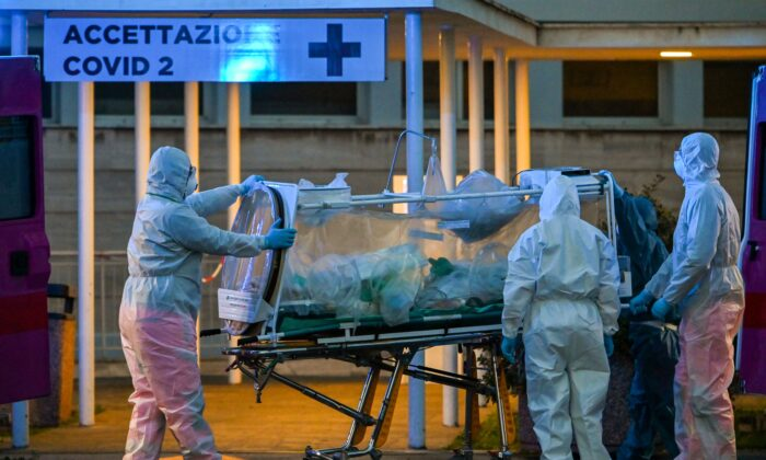 Medical workers in coveralls wheel a patient under intensive care into the newly built Columbus Covid 2 temporary hospital to fight the CCP virus, at the Gemelli hospital in Rome on March 16, 2020. (Andreas Solaro /AFP via Getty Images)