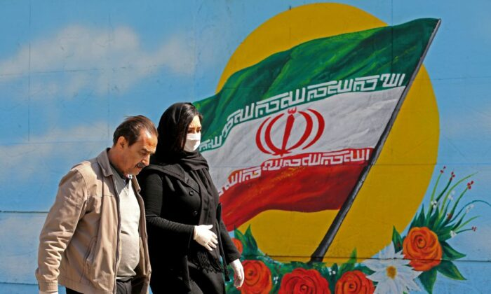 Iranians wearing masks walk past a mural displaying their national flag in Tehran on March 4, 2020. (Atta Kenare/AFP via Getty Images)