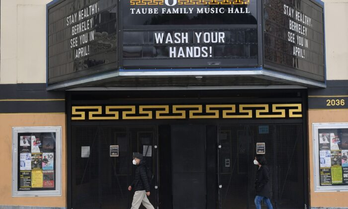 People wearing face masks walk by a closed theater with a message about staying healthy in Berkeley, Calif., on March 18, 2020. (Josh Edelson/AFP via Getty Images)