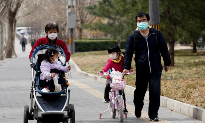 A Chinese family wearing a protective facemask at a park in Beijing, China, on March 19, 2020. (Lintao Zhang/Getty Images)