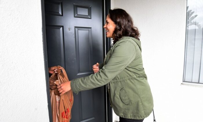 A customer reaches out as Instacart employee Monica Ortega delivers groceries in an apartment complex in North Hollywood, Calif., on March 19, 2020. (Frederic J. Brown/AFP via Getty Images)