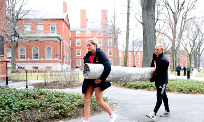 Sophomore Sophie Butte helps freshman Alex Petty move his rug across Harvard Yard on the campus of Harvard University in Cambridge, Mass., on March 12, 2020. (Maddie Meyer/Getty Images)