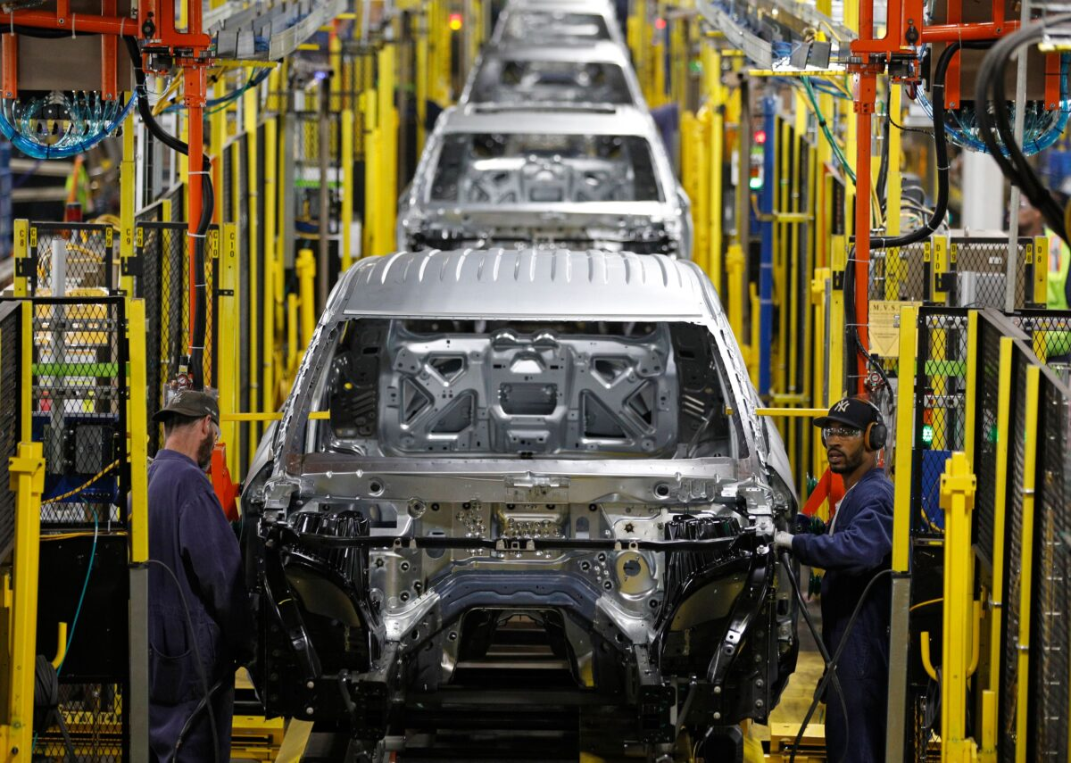 Workers assemble cars