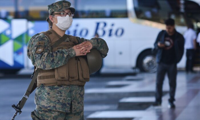A Chilean soldier wears a protective mask as they stand guard inside a bus station in Concepcion, Chile, on March 19, 2020. (Guillermo Salgado/AFP via Getty Images)