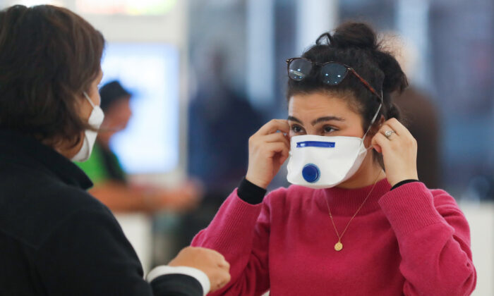 A passenger at Sydney airport covers her face with a mask in Sydney, Australia on March 16, 2020. (Brendon Thorne/Getty Images)