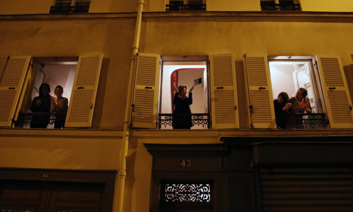 Parisians, in spirit at least, applaud the caregivers and police for their work, as the coronavirus ravaged communities across the country, in Paris, Wednesday, March 18, 2020. (Francois Mori/AP)