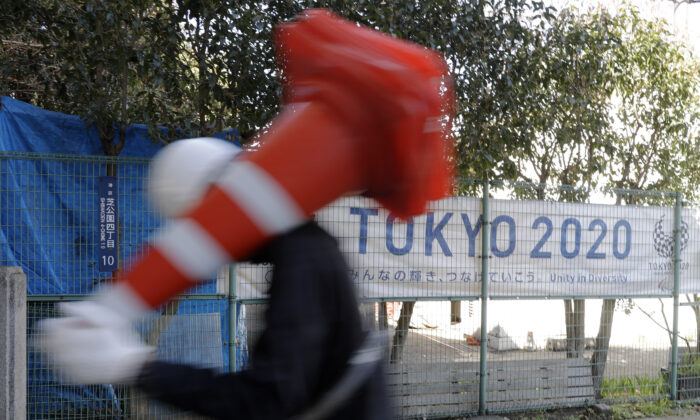 A worker on duty at a road construction site walks past a banner promoting the 2020 Olympic Games in Tokyo, on March 20, 2020. (Gregorio Borgia/AP Photo)