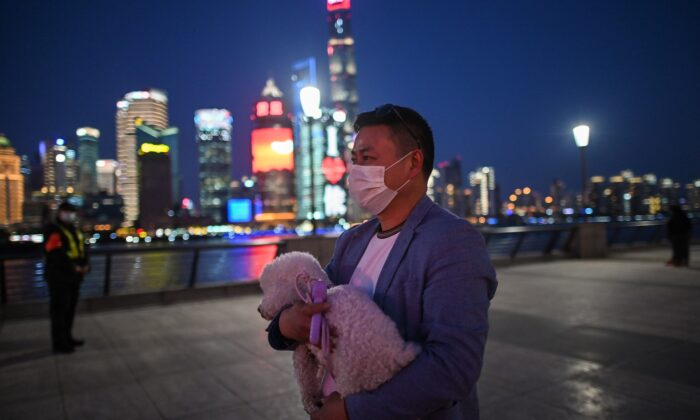 A man wearing a face mask amid concerns over the CCP virus outbreak walks holding his dog along the promenade of the Bund along Huangpu River in Shanghai, China, on March 20, 2020. (Hector Retamal/AFP via Getty Images)