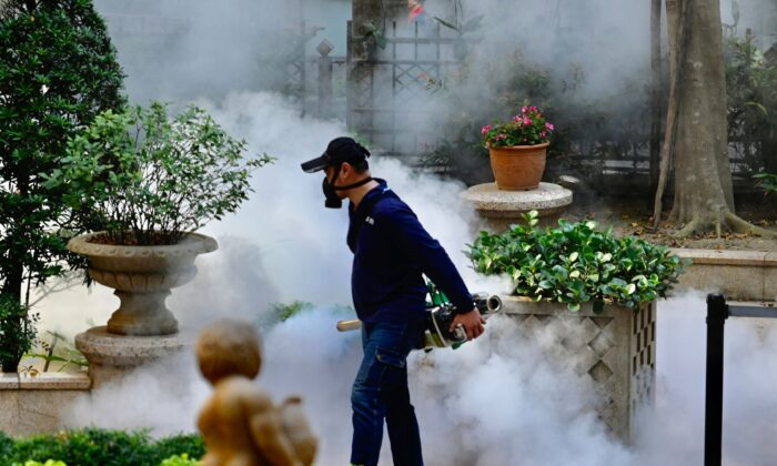 A mask-clad worker disinfects an area in Xindian district in New Taipei City on March 9, 2020. (Sam Yeh/AFP via Getty Images)