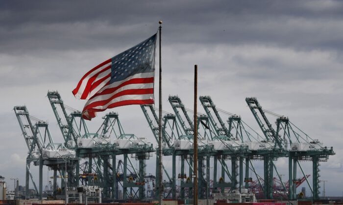 The US flag flies over shipping cranes and containers after a report said the United States and China are close to reaching a major trade deal that would see both sides lower some of the tariffs imposed during an often-bitter trade war, in Long Beach, California on March 4, 2019. (Photo by MARK RALSTON/AFP via Getty Images)